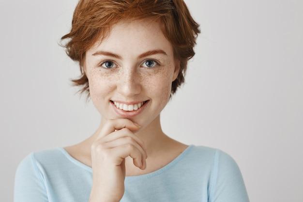 Zbliżenie: atrakcyjna ruda dziewczyna uśmiecha się kusząco i szuka
