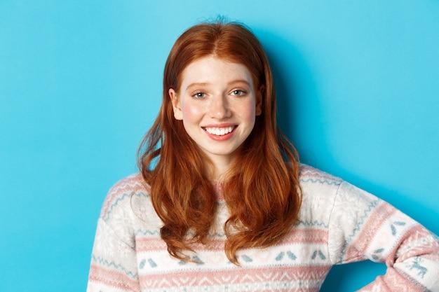 Zbliżenie: atrakcyjna studentka z rudymi włosami, ubrana w zimowy sweter, uśmiechnięta szczęśliwa i wpatrująca się w kamerę, niebieskie tło.