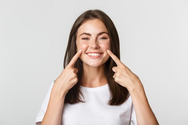 Zbliżenie: atrakcyjna uśmiechnięta młoda dziewczyna, wskazując palcami na twarz, szturchając policzki, biały.