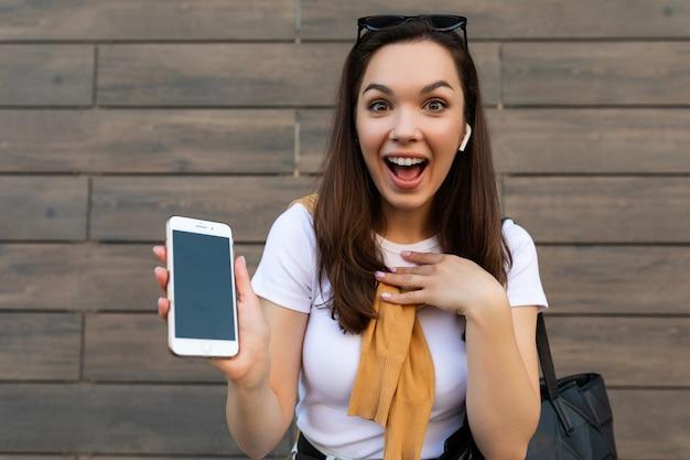 Zbliżenie atrakcyjna zszokowana zdziwiona młoda kobieta ubrana w zwykłe ubrania stojąca na ulicy