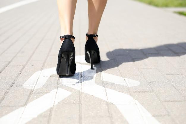 Zbliżenie: atrakcyjne kobiece nogi w czarnych eleganckich butach na wysokim obcasie. kobieta idzie na chodniku. słoneczny poranek lub dzień. długie zgrabne stopy. koncepcja odwołania kobiet