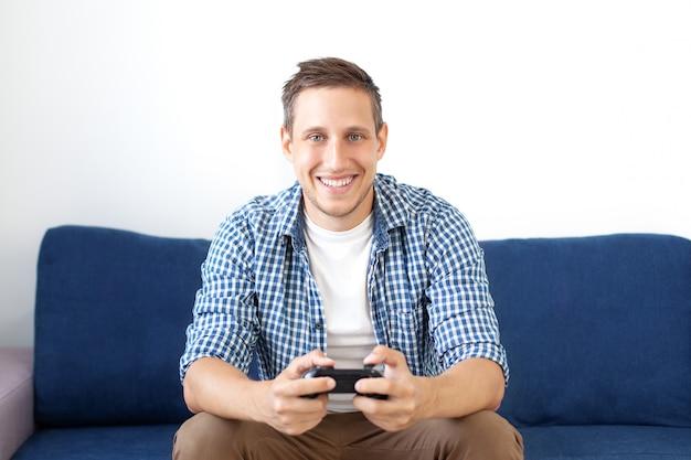 Zbliżenie atrakcyjnego faceta z zarostem w koszuli, trzymającego joystick i grającego w gry wideo w telewizji na wakacjach, siedzi w domu na wygodnej kanapie, odnosi sukcesy, wygrywa w wyścigach samochodowych. gracz gra na konsolę