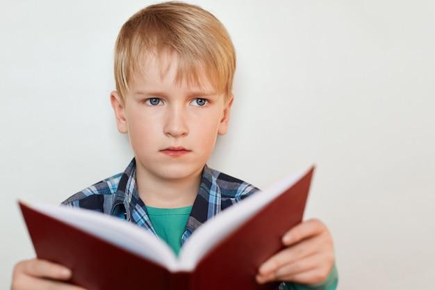 Zbliżenie atrakcyjnego ucznia o niebieskich oczach i blond włosach ubranego w kraciastą koszulę trzymającego w rękach książkę o zamyślonym wyrazie twarzy, marzącą o czymś stojącym w pobliżu białej ściany