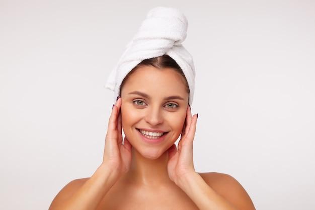 Zbliżenie atrakcyjnej młodej damy z ciemnymi włosami owiniętymi w ręcznik, dotykając jej twarzy z uniesionymi rękami i patrząc wesoło z szerokim uśmiechem, stojąc na białym tle