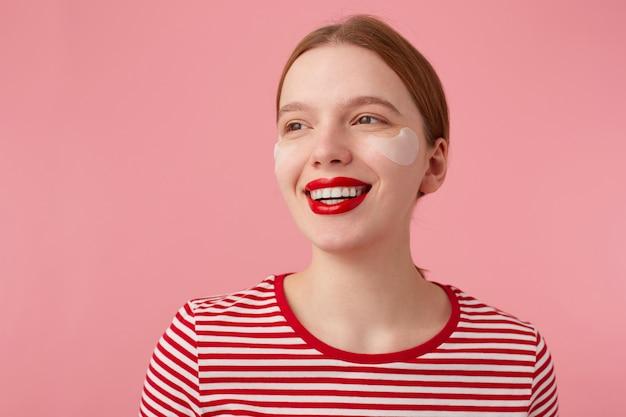 Zbliżenie atrakcyjnej młodej, uśmiechniętej rudowłosej kobiety z czerwonymi ustami i łatami pod oczami, nosi czerwoną koszulkę w paski, odwraca wzrok ze szczęśliwym wyrazem twarzy, stoi.