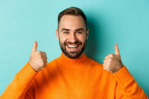 Zbliżenie: atrakcyjny brodaty mężczyzna pokazuje kciuk w górę, zatwierdza i lubi, poleca produkt, jasnoniebieskie tło.