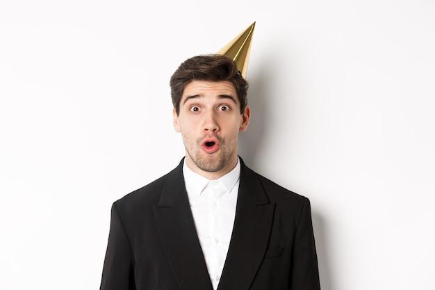 Zbliżenie: atrakcyjny mężczyzna w partyjnym kapeluszu i modnym garniturze, patrząc zaskoczony, świętuje nowy rok, stojąc na białym tle.