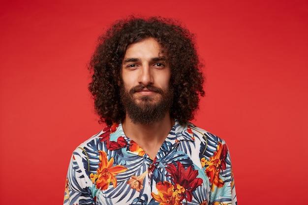 Zbliżenie: atrakcyjny młody brunetka mężczyzna z bujną brodą i kręconymi włosami, który pozytywnie patrzy na aparat i uśmiecha się lekko, trzymając usta złożone podczas pozowania na czerwonym tle