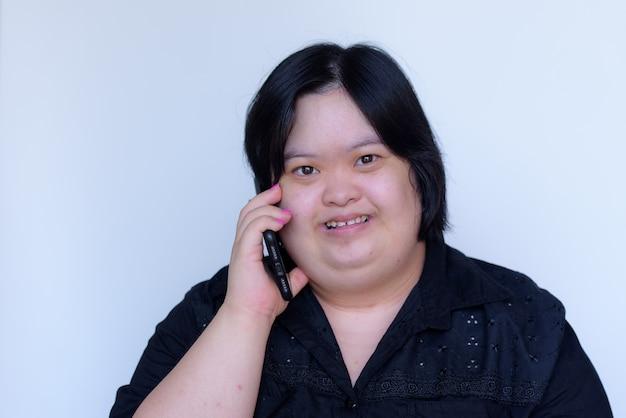 Zbliżenie: azjatycka dziewczyna z niepełnosprawnością. dzieci z zespołem downa. rozmawia przez telefon i uśmiecha się szczęśliwy na białym tle