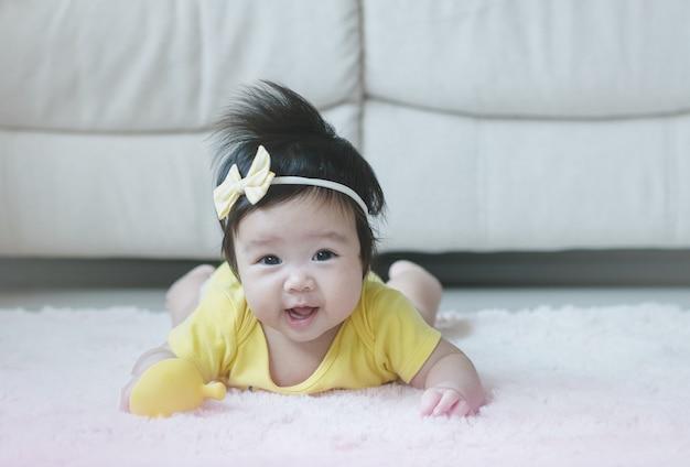 Zbliżenie azjatycka dziewczynka leży na dywanie w sprytnym ruchu