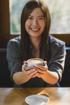 Zbliżenie azjatycka młoda kobieta trzyma filiżankę kawy w nowoczesnej kawiarni lub przestrzeni coworkingowej
