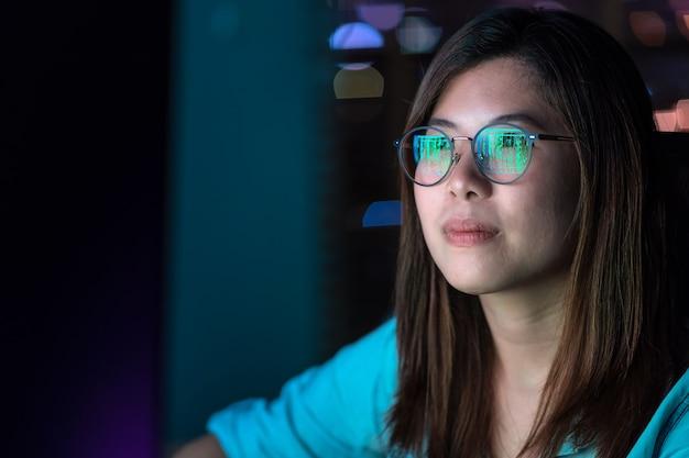 Zbliżenie azjatycki bizneswoman pracuje mocno i patrzeje cyfrową grafikę na stole