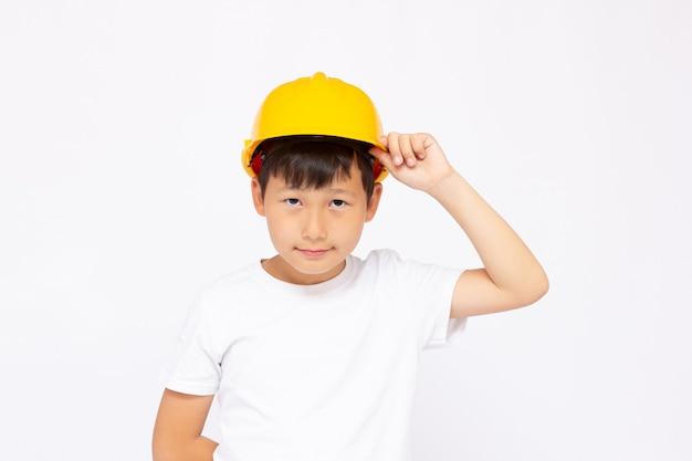 Zbliżenie: azjatycki chłopiec ubrany w kask uśmiechający się i patrzący na kamerę, stojący na białym tle.