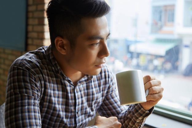 Zbliżenie azjatycki mężczyzna ma jego ranek kawę przy okno