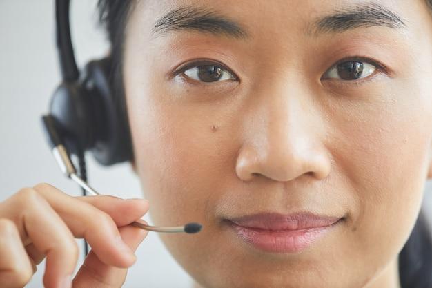 Zbliżenie: azjatycki młody operator szuka słuchawek