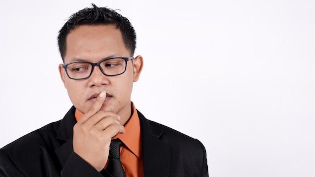 Zbliżenie azjatyckiego biznesmena myślenia na białym tle