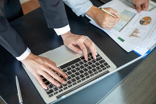 Zbliżenie azjatyckiego biznesmena używającego dokumentów analizy laptopa i wykresu finansowego diagramu na biurowym stole roboczym