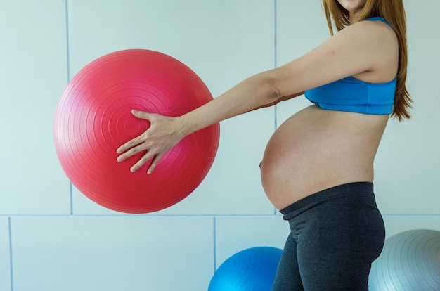 Zbliżenie azjatykcia ciężarna kobieta ćwiczy w pokoju sportowym, trzyma dużą piłkę