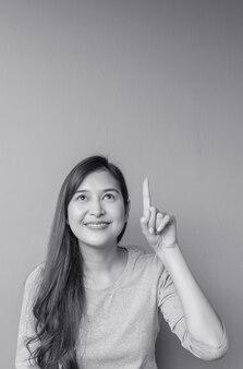 Zbliżenie azjatykcia kobieta podtrzymuje jeden palca punkt przestrzeń z uśmiech twarzą na zamazanym cementu ścianie textured tło