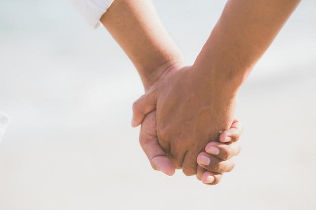 Zbliżenie azjatykciej homoseksualnej pary mienia ręki wpólnie na plaży.