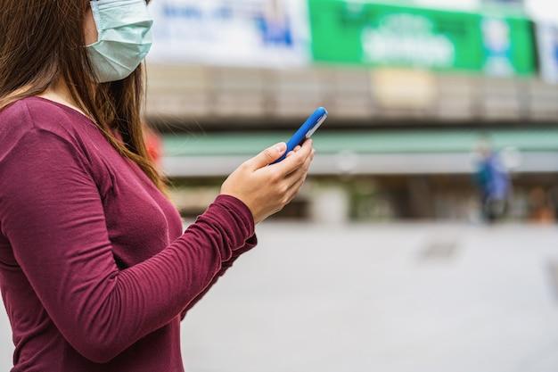 Zbliżenie azji kobieta ręka za pomocą inteligentnego telefonu komórkowego z bezpieczną maską medyczna na twarz