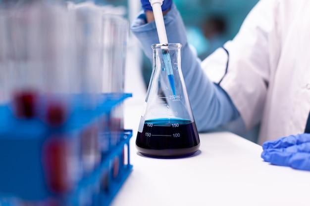 Zbliżenie badania profesjonalnego naukowca pobierającego próbkę z probówki za pomocą mikropipety