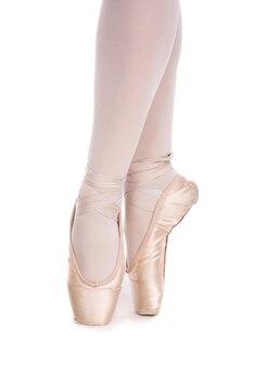 Zbliżenie baleriny w pointe butach pozujących na białym tle