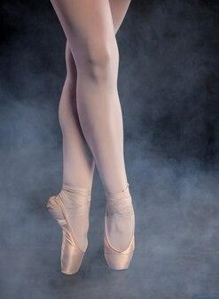 Zbliżenie baleriny w pointe butach pozujących na ciemnym zadymionym tle