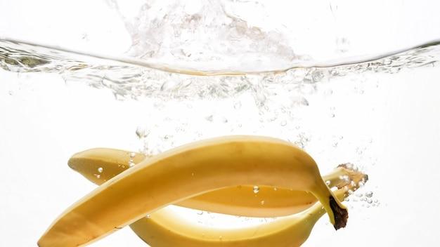Zbliżenie bananów spadających w czystej wodzie