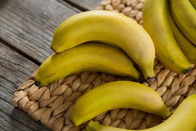 Zbliżenie bananów trzymanych na podkładce na drewnianym stole