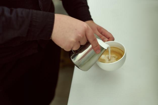 Zbliżenie: barista trzymający filiżankę kawy i wlewając mleko