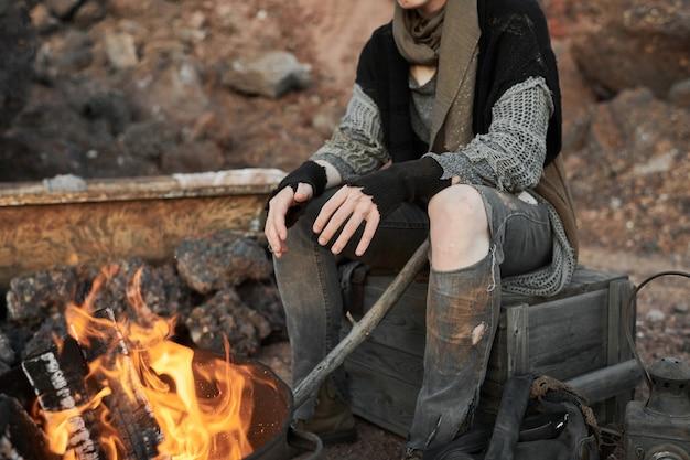 Zbliżenie bezdomnej kobiety w podartych ubraniach rozgrzewa się w pobliżu ognia na zewnątrz