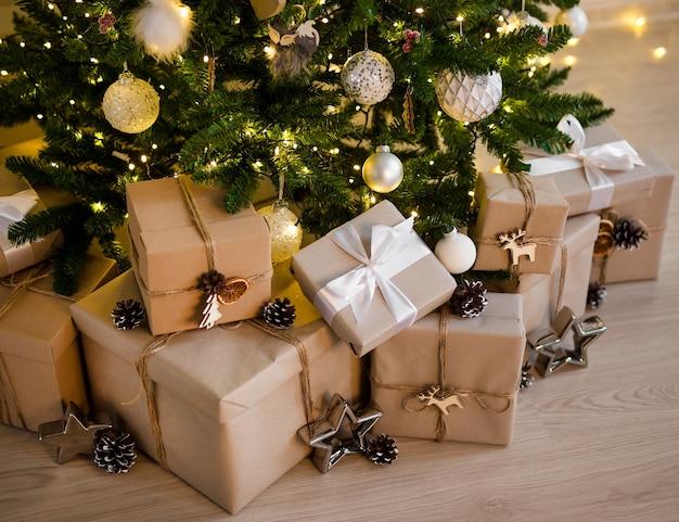 Zbliżenie beżowych pudełek prezentowych pod ozdobną choinką ze światłami