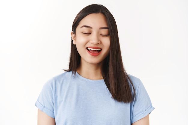 Zbliżenie beztroski pozytywny zrelaksowany uroczy azjatycki szczęśliwy dziewczyna zamknij oczy uśmiechnięty zachwycony śpiew wyraża głębokie emocje duszy nieśmiały spojrzenie liczenie do zobaczenia niespodzianka prezent stoisko biała ściana