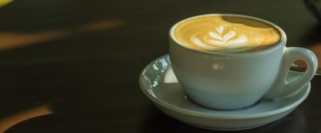 Zbliżenie biała filiżanka gorący kawowy latte z mleko pianą na drewnianym stole w ranku świetle słonecznym i cienia use dla pojęcia tapety lub okładkowej strony.