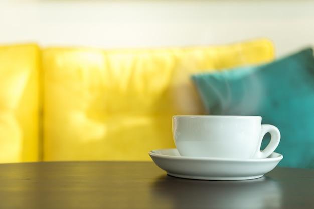 Zbliżenie biała filiżanka gorący kawowy latte z mleko pianą na drewnianym stole w ranku świetle słonecznym w restauracyjnym use dla tapety lub okładkowej strony pojęcia.