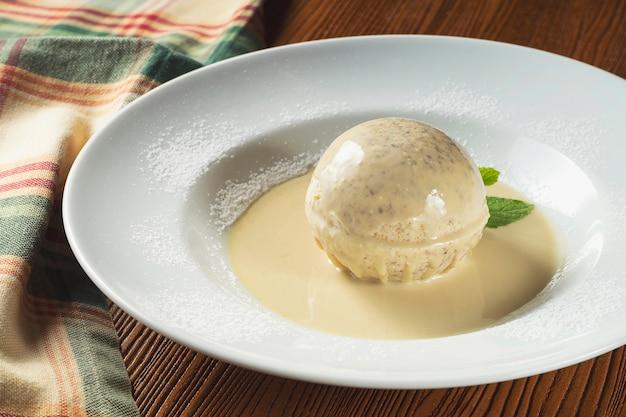 Zbliżenie białe lody włoskie w białą czekoladową kulkę ze stopioną białą czekoladą na talerzu z miętą.