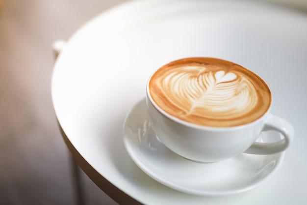 Zbliżenie biały kubek gorącej kawy latte ze sztuką w kształcie serca pianki mlecznej na talerzu na białym stole z miejsca na kopię.