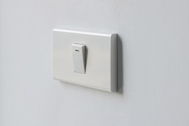 Zbliżenie biały przełącznik do oświetlenia ściennego i biurowego do użytku biurowego i mieszkalnego.