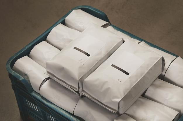 Zbliżenie biały wypełniony zapieczętowanymi opakowaniami kawy lub herbaty w plastikowym pudełku na betonowej podłodze w magazynie.