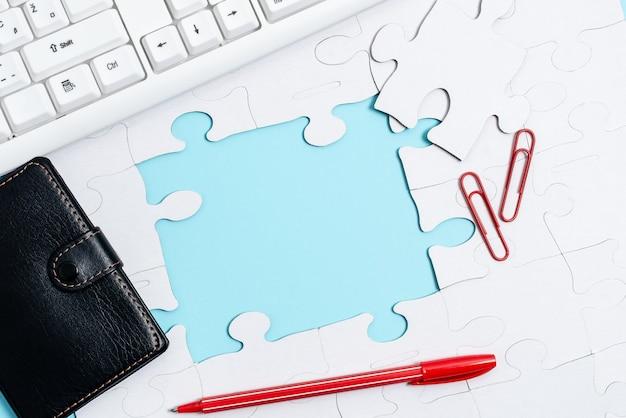 Zbliżenie biały wzór układanki do połączenia z brakującym ostatnim elementem umieszczonym na płaskim ułożonym tle z różnymi teksturami i akcesoriami do papieru