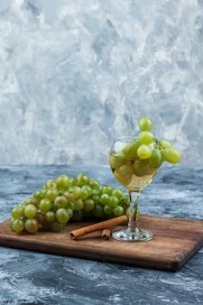 Zbliżenie białych winogron, kieliszek whisky, cynamon na desce do krojenia na ciemnym i jasnoniebieskim tle marmuru. pionowy