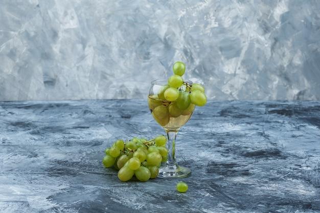 Zbliżenie białych winogron, kieliszek whisky na ciemnym i jasnoniebieskim tle marmuru. poziomy
