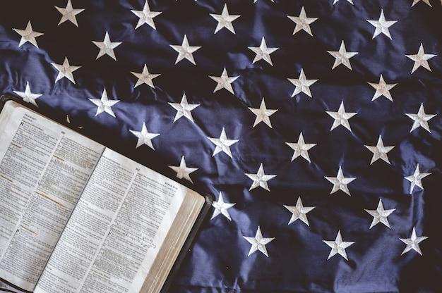 Zbliżenie biblii otwarte na stronach umieszczonych na amerykańskiej fladze - idealne do modlitwy