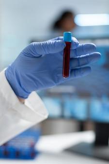 Zbliżenie biologa badacza mężczyzny trzymającego medycznego vacutainer z próbką krwi