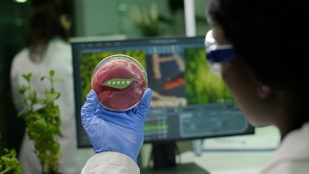 Zbliżenie biologa trzymającego w rękach próbkę wegańskiego mięsa wołowego