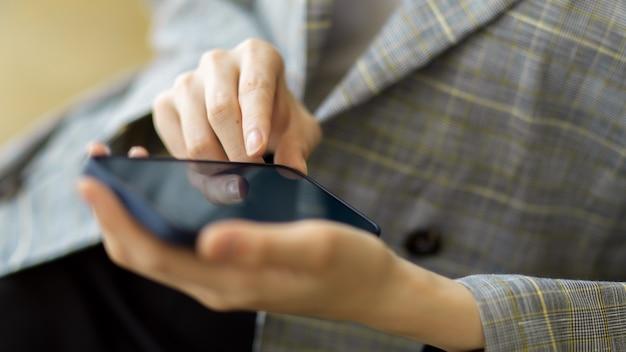 Zbliżenie biznes kobieta w modnym garniturze za pomocą inteligentnego telefonu komórkowego do kontaktu
