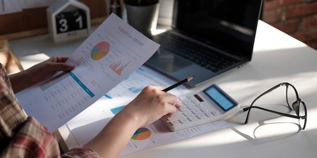 Zbliżenie biznesmen lub księgowy ręka trzyma pióro pracujące na kalkulatorze do obliczania danych biznesowych, dokumentu księgowego i laptopa w biurze, koncepcja biznesowa
