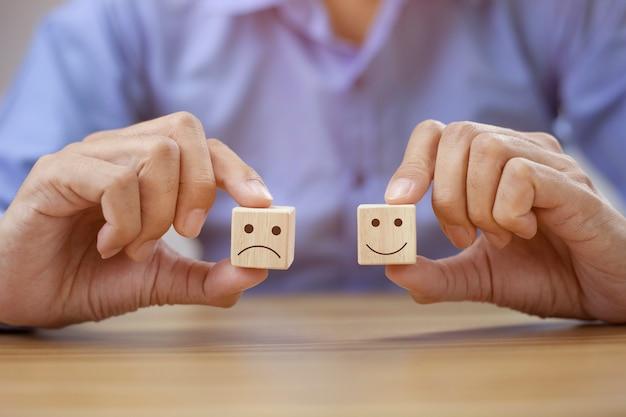 Zbliżenie biznesmen pokazując ocenę z uśmiechniętą twarz i smutną twarz ikoną
