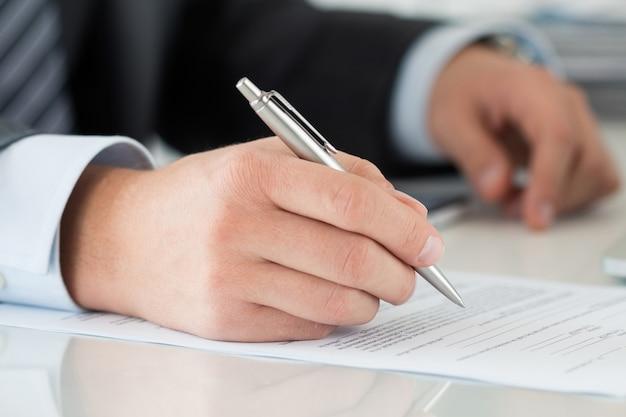 Zbliżenie: biznesmen ręce podpisywanie dokumentów